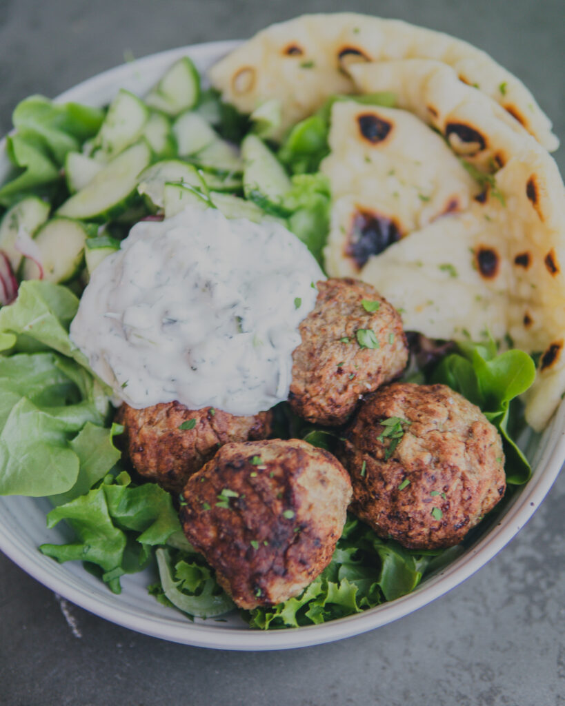 AirCrisp Greek Meatballs w/ Cucumber Salad in a large salad bowl with naan bread.